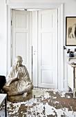 Grosse Buddhafigur auf Boden mit abblätternder Farbe vor weisser Flügeltür