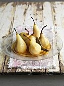 Poached vanilla pears in syrup on a glass plate
