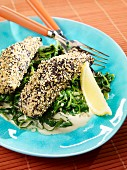 Steamed salmon fillets with a sesame and poppy seed coating on a bed of spinach