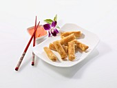 Spring rolls with chilli sauce, chopsticks and an orchid (China)
