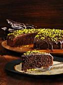 Carob cake with a chocolate glaze and pistachio nuts