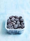 Frozen blackberries in a plastic punnet