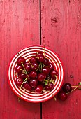 Fresh cherries on a stripped plate (seen from above)