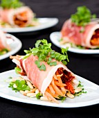 Parma ham rolls on a watercress salad with pine nuts