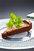 A slice of brownie cake garnished with lemon balm
