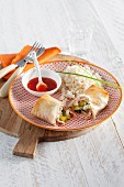 Puff pastry rolls filled with vegetables and ham served with rice and chilli sauce