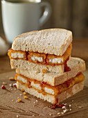 A fish finger sandwich with tomato ketchup on a wooden board