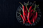 Fresh red chilli peppers on a plate (seen from above)