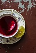 A cup of fruit tea with a teabag