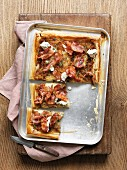 A puff pastry tart on a baking tray with onions, bacon, ricotta and thyme, sliced