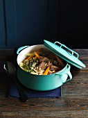 Pork stew with vegetables and tender wheat in a light blue enamel pot