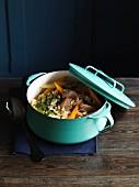 Eintopf mit Schweinefleisch, Gemüse und Zartweizen in hellblauem Emailletopf