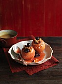 Two baked apples with fruit and nuts on a ceramic plate