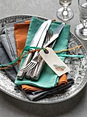 Silver cutlery with a label and ribbons on coloured napkins