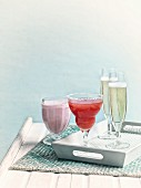 A strawberry milkshake, a strawberry margarita and glasses of champagne on a wooden tray