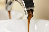 Hot espresso running into two cups