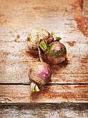 Three organic turnips on a wooden surface