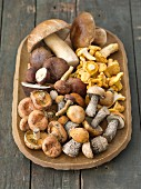 Fresh wild mushrooms in a brown dish on a rustic table