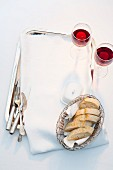 Slices of baguette in a breadbasket, a butter dish and glasses of red wine on the tray