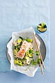 Salmon on a bed of oriental noodles with leek in parchment paper