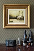 Parfumflakon zwischen Schatulle und Sammlerstücken auf Ablage, an Wand gerahmtes Bild in Gold