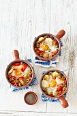 Baked eggs with potatoes, peppers, onions, olives and tomatoes