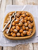 Hazelnuts in a wooden bowl with a nutcracker