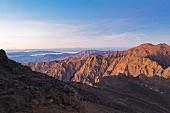 Tiefrot glühen die Felshänge am Djebel Toubkal morgens um kurz vor sieben, Marokko