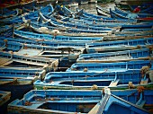 Blue wooden fishing boats moored close together in the harbour of Essaouira, Morocco