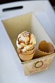 Vanilla ice cream with caramel sauce and chopped nuts in an ice cream cone