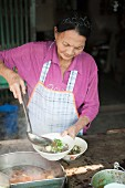 An older woman serving noodle soup, Thailand