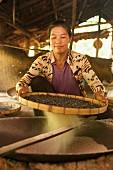 Thailändische Frau beim Rösten von Erdnüssen auf traditionelle Art