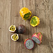 Various exotic fruits on a wooden surface over (passion fruit, red pitahaya, kiwano)