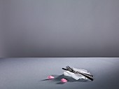 Cutlery on a fabric napkin and pink rose petals on a grey surface