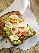 Grilled bread topped with avocado, bananas and chillis