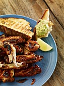 Grilled chicken wings with bread and an avocado dip