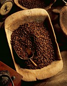 Coffee beans in a wooden bowl with a scoop, an old coffee grinder and a pair of kitchen scales