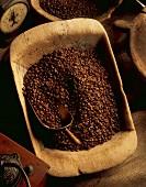 Kaffeebohnen in Holzschale mit Schaufel, alte Kaffeemühle und Küchenwaage