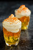 Layered yellow and orange jelly topped with whipped cream and orange sugar sprinkles