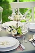 Silber Etagere mit weissen Blumen verziert auf gedeckter Hochzeitstafel