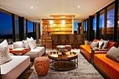 Lounge mit Blick durch umlaufende Fensterfront in den Abendhimmel