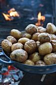 A pan of baked potatoes in front of a glowing grill