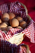 Fresh eggs in a basket lined with a checked cloth