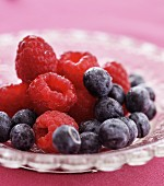 Fresh raspberries and blueberries in a glass bowl