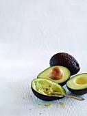 Avocados, ganz, halbiert und ausgehöhlt