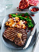 A beef steak with mashed sweet potatoes, pomegranate seeds and broccoli