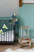 Holzstuhl mit abgeblätterter Farbe und dunkles Gitterbett mit Wimpelkett und Häkeldecke