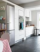 Zeitgenössische Küche mit weissen Einbauschränken und integriertem Kühlschrank aus Edelstahl
