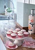 Verzierte Muffins in rosa Förmchen auf weisser Etagere