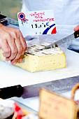 Mann beim Käseschneiden